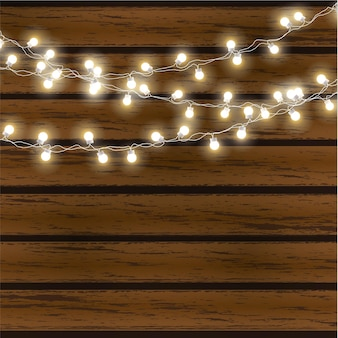 Lampki choinkowe na białym tle na ciemnym tle drewniane. świecąca girlanda.