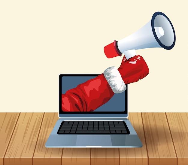 Laptop i ręka trzyma megafon nad drewnianym