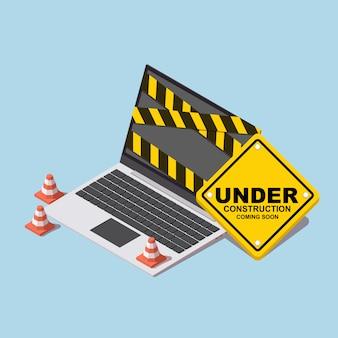 Laptop z budowy stożka i znak budowy.