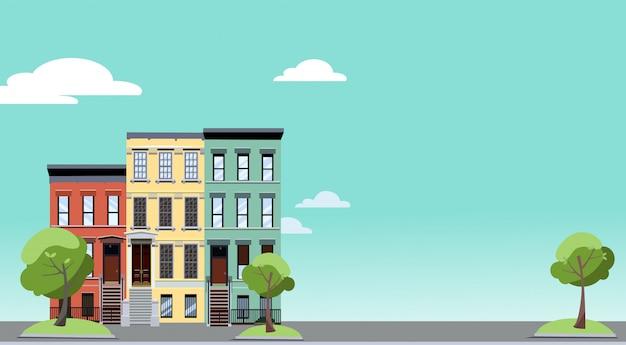 Lato w mieście. kolorowy krajobraz miejski z przytulnymi zielonymi drzewami w pobliżu dwupiętrowych domów.