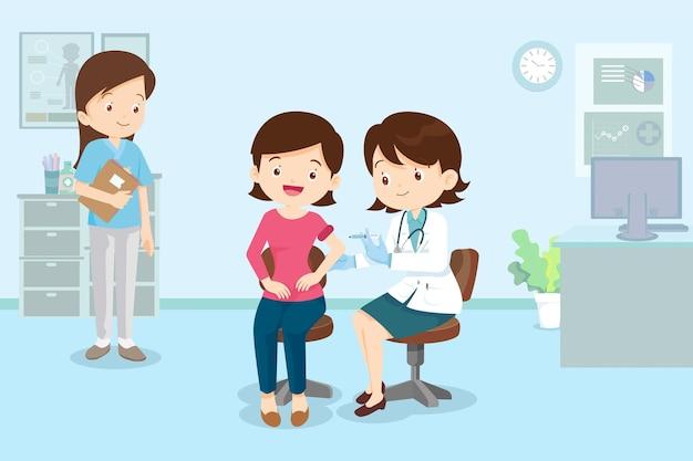 Lekarz wstrzykuje szczepionkę covid19 dla kobietpodając kobiecie szczepionkę na koronawirusa