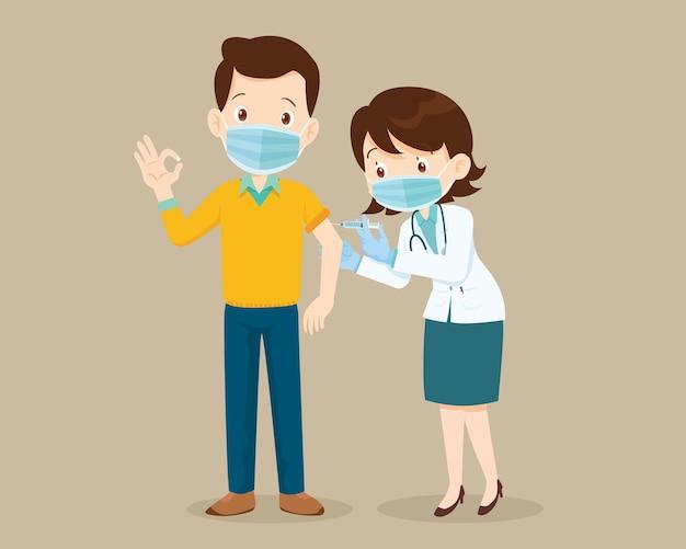 Lekarz wstrzykuje szczepionkę przeciwko koronawirusowi szczepienie covid19 dla mężczyzny pokazującego dobry gest