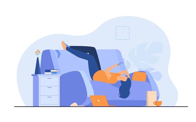 Leniwa przygnębiona kobieta odpoczywa na kanapie ze smartfonem po zrobieniu bałaganu w domu.