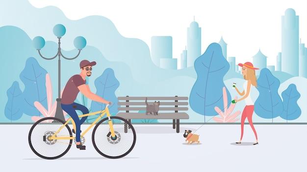 Letni park miejski. dziewczyna z psem spaceruje po parku. facet na rowerze.