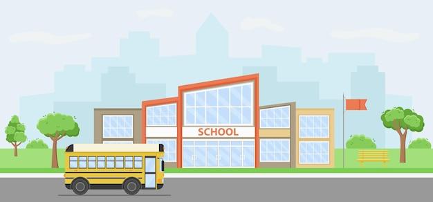 Letni pejzaż miejski z budynkiem szkoły i żółtym autobusem.
