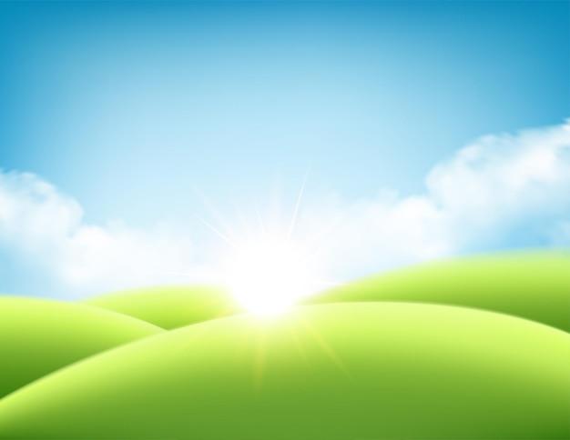 Letni wschód słońca w tle, krajobraz z zielonymi wzgórzami i łąkami, błękitne niebo i chmury.