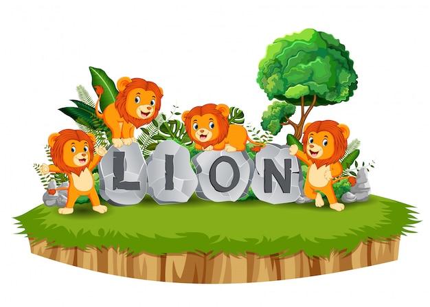 Lew grają razem w ogrodzie z kamienną literą