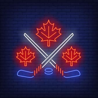 Liście klonu z skrzyżowanymi neonowymi kije hokejowe