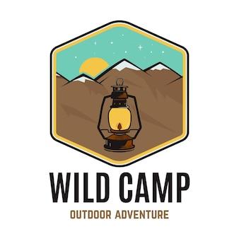Logo dzikiego obozu, przygoda na świeżym powietrzu retro camping przygoda emblemat z górami. wektor