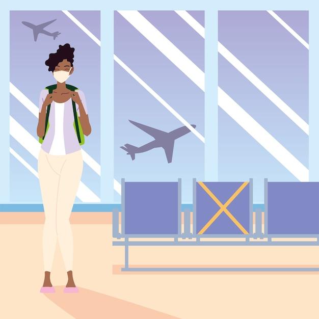 Lotnisko nowa normalna, młoda afroamerykańska kobieta z maską i plecakiem czeka na lot