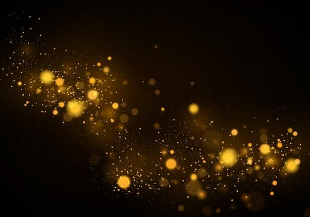 Lśniące magiczne złoto-żółte cząsteczki pyłu. czarne tło z efekt bokeh.