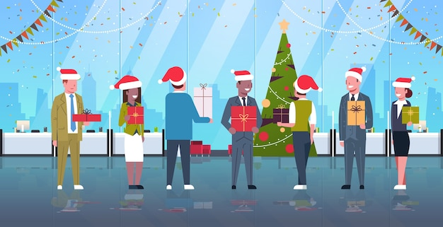 Ludzie biznesu świętujący imprezę firmową mieszankę wyścigu współpracownicy w czapkach mikołaja trzymający pudełka z prezentami wesołych świąt szczęśliwego nowego roku wakacje koncepcja nowoczesne wnętrze biura