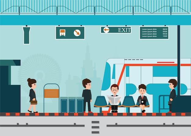 Ludzie czekają na pociąg na peronie dworca.