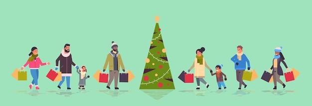 Ludzie idący z zakupami wesołych świąt szczęśliwego nowego roku koncepcja zimowych zakupów rodzice z dziećmi trzymając papierowe torby stojące w pobliżu jodły