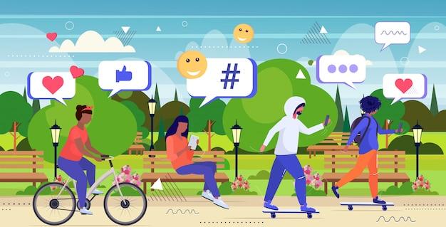 Ludzie korzystający z aplikacji mobilnej online sieć mediów społecznościowych czat bańka komunikacja cyfrowa koncepcja uzależnienia mieszanka rasa mężczyźni kobiety spacery w parku krajobraz tło szkic pełna długość poziomy