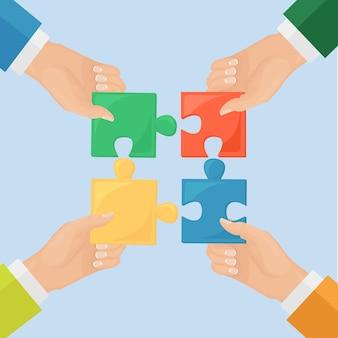 Ludzie łączący elementy układanki. metafora pracy zespołowej, współpracy, partnerstwa. pomysł na biznes