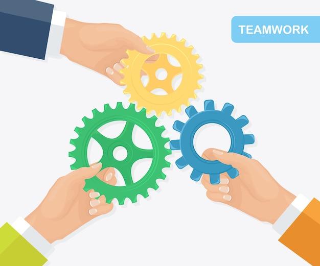 Ludzie łączący koła zębate. metafora pracy zespołowej, współpracy, partnerstwa. pomysł na biznes