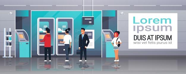 Ludzie oczekujący na samoobsługowy bankomat