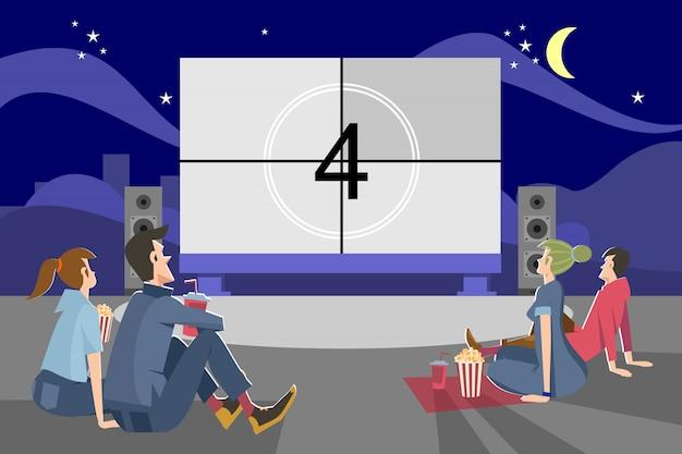 Ludzie oglądają film wieczorem na zewnątrz