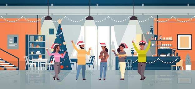 Ludzie podnoszący ręce picie kawy mężczyźni kobiety w czapkach mikołaja zabawa boże narodzenie nowy rok ferie zimowe koncepcja uroczystości nowoczesna kawiarnia