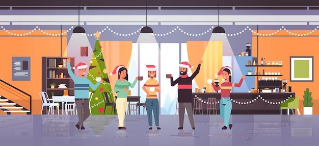 Ludzie podnoszący ręce picie kawy mężczyźni kobiety w czapkach mikołaja zabawa wesołych świąt szczęśliwego nowego roku ferie zimowe koncepcja uroczystości nowoczesne wnętrze kawiarni mieszkanie