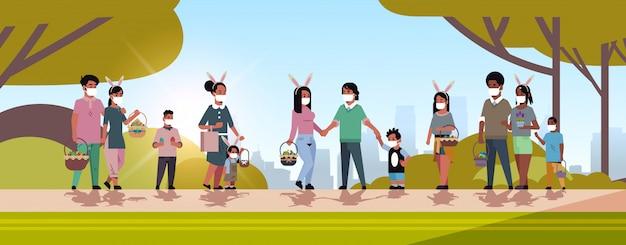 Ludzie rasy mieszanej trzymają kosze z jajami w maskach, aby zapobiec koronawirusowi świętującemu wielkanoc