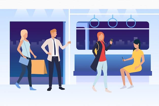 Ludzie siedzący i stojący w pociągu metra
