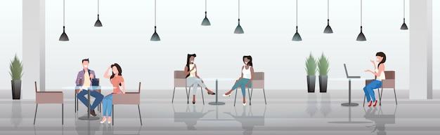 Ludzie siedzący przy stolikach w kawiarni dyskutujący podczas spotkania nowoczesnych w restauracji