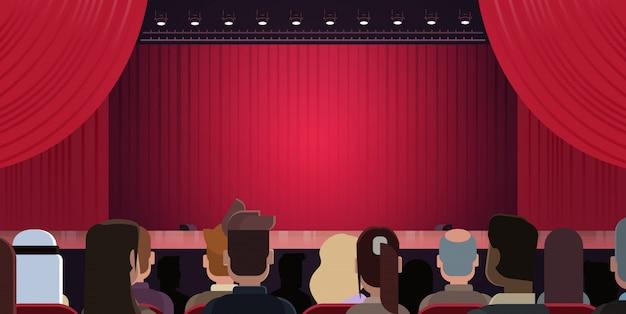 Ludzie siedzi przy teatrem lub w kinie patrząc na scenę z czerwonymi zasłonami czeka na występ st