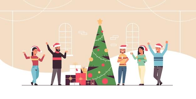 Ludzie świętują wesołych świąt i szczęśliwego nowego roku święto uroczystości wigilia partii koncepcja mężczyźni kobiety w czapkach świętego mikołaja piją szampana płaska pełna długość pozioma ilustracja wektorowa