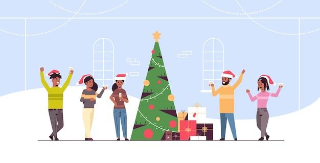 Ludzie świętujący wesołych świąt i szczęśliwego nowego roku święto uroczystość wigilia party koncepcja afroamerykanie mężczyźni kobiety noszący czapki mikołaja piją szampana płaskie pełnej długości poziome wektor illustra