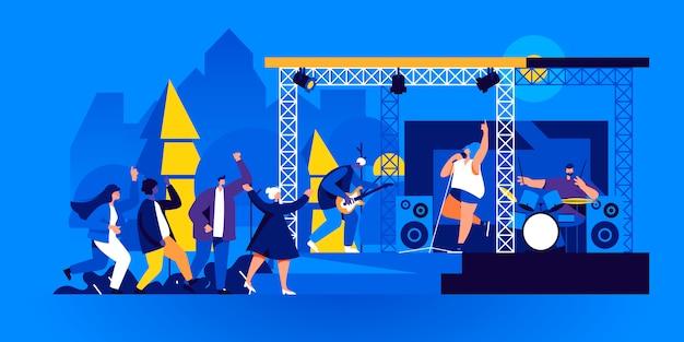 Ludzie tańczą przed sceną plenerową z występami zespołu muzycznego