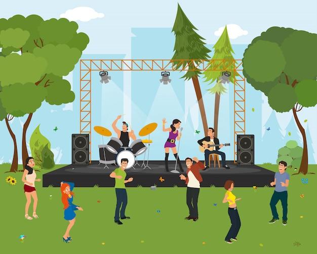 Ludzie tańczą w parku miejskim na koncercie.