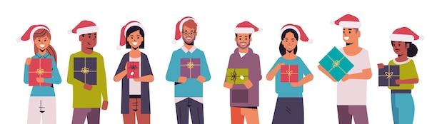 Ludzie trzymający prezent pudełka wesołych świąt szczęśliwego nowego roku wakacje uroczystość koncepcja mieszanka rasa mężczyźni kobiety w czapkach mikołaja stojąc razem poziome portret ilustracji wektorowych