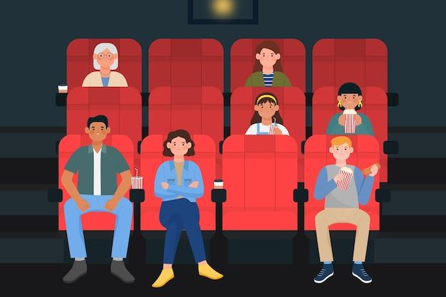 Ludzie trzymający się z dala od siebie w kinie