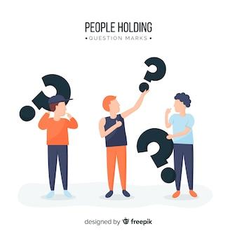 Ludzie trzymający znaki zapytania