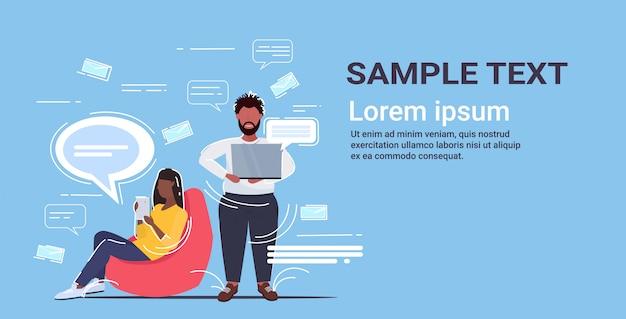 Ludzie używający gadżetów aplikacja internetowa sieć społeczna czatowanie komunikacja koncepcja afroamerykanin mężczyzna kobieta z czat bańka mowy poziomej pełnej długości kopia przestrzeń