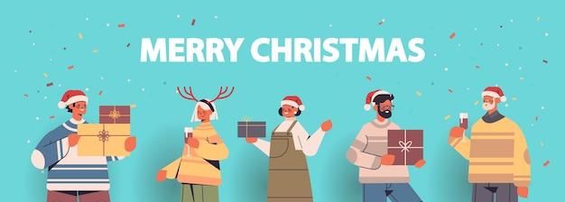 Ludzie w czapkach świętego mikołaja zabawy z prezentami pudełka na prezenty szczęśliwego nowego roku i wesołych świąt bożego narodzenia koncepcja uroczystości poziome portret ilustracji wektorowych