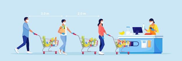 Ludzie w maskach z wózkami i koszami na zakupy czekają w kolejce przy kasie. dystans społeczny i zapobieganie koronawirusowi covid-19. zachowaj bezpieczną odległość od innych osób w supermarkecie
