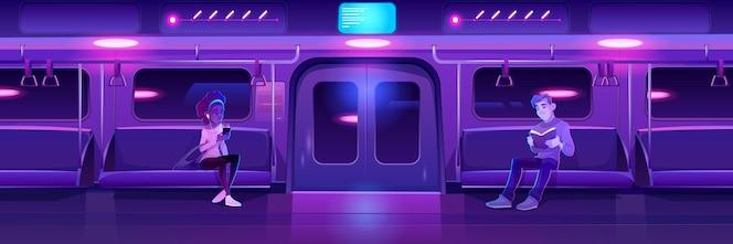 Ludzie w nocnym pociągu metra kobieta z telefonem i człowiekiem z książką w wagonie metra z neonowym świecącym oświetleniem