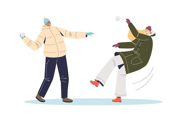 Ludzie w zimowych ubraniach grający w śnieżki. młody mężczyzna i kobieta walka na piłkę śnieżną. gry i zabawy zimowe.
