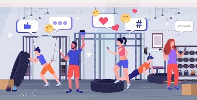 Ludzie wykonujący ćwiczenia fizyczne przy użyciu aplikacji mobilnej online w sieci mediów społecznościowych komunikacja cyfrowa koncepcja treningu uzależnień nowoczesne wnętrze siłowni szkic pełnej długości w poziomie