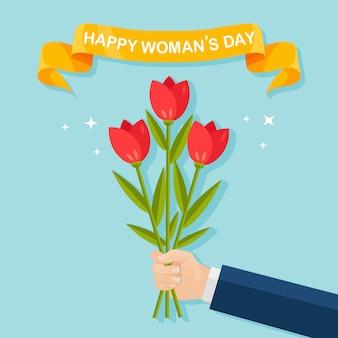 Ludzka ręka trzyma bukiety lub bukiety kwitnących kwiatów