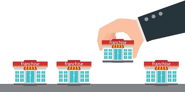 Ludzką ręką trzyma mały sklep lub franczyzy.