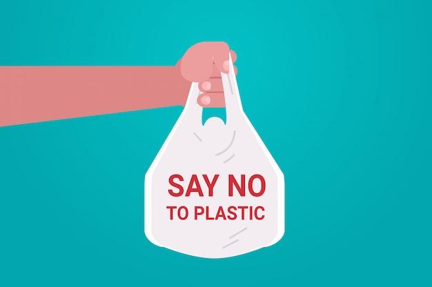 Ludzką ręką trzyma worek powiedzieć, że nie ma plastikowych zanieczyszczeń recyklingu problem ekologii uratować pojęcie ziemi płasko poziomo