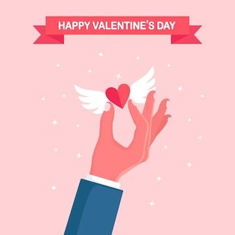 Ludzką ręką trzymać czerwone serce ze skrzydłami. szczęśliwych walentynek. romans, koncepcja miłości