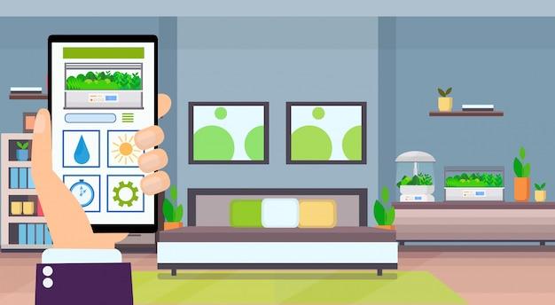 Ludzką ręką za pomocą aplikacji mobilnej inteligentne sterowanie roślinami system uprawy koncepcja ekran smartfona nowoczesne mieszkanie wnętrze sypialni z terrarium szklany pojemnik płaski poziomo