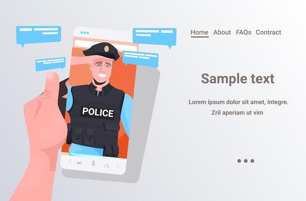Ludzką ręką za pomocą smartfona na czacie z policjantem podczas połączenia wideo