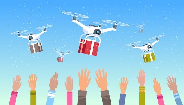 Ludzkie ręce podniesione do góry drony dostarczające prezenty obecne pudełka transport niebo wysyłka poczta lotnicza koncepcja ekspresowej dostawy