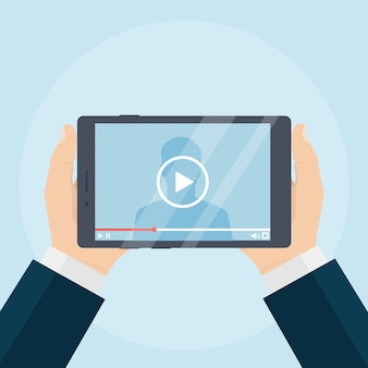 Ludzkie ręce, trzymając komputer typu tablet z odtwarzaczem wideo na ekranie